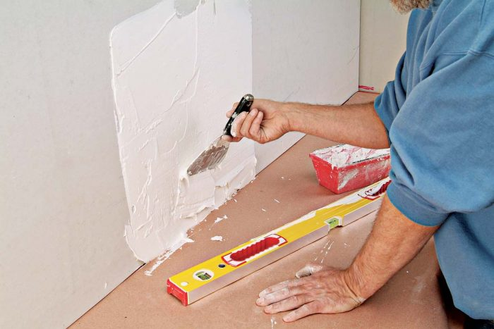 Flatten the wall by filling hollows with quick-setting wall patch compound.