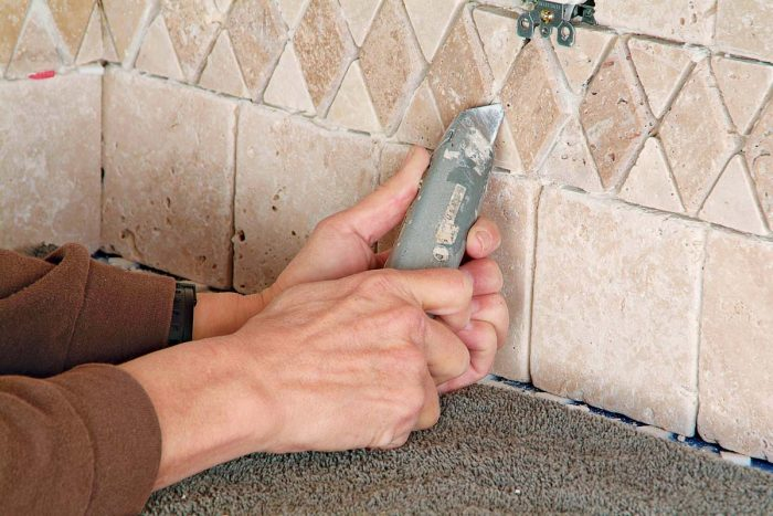 Use both hands to steady the utility knife as you scrape thinset from between grout lines. A slip can scratch stone tiles.