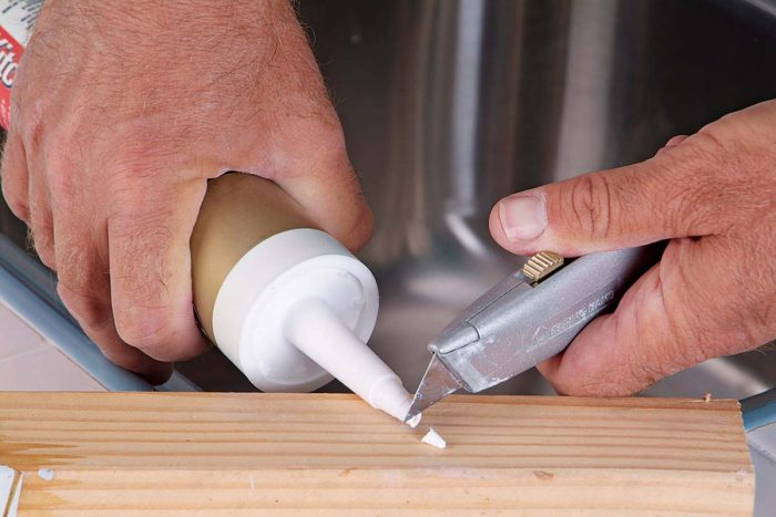 Slice off the tip of the caulk tube at an angle. Cut it near the top of the tube to ensure a small opening.
