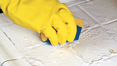 Scrub the grout and tile surface with the rough, nonmetallic side of the sponge.