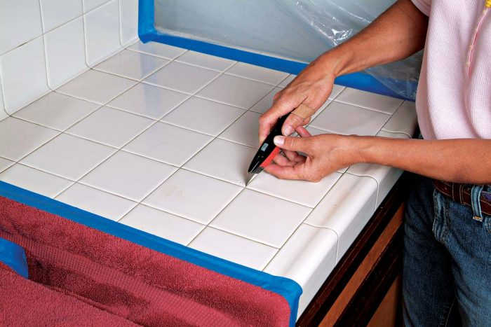 A utility knife can remove softer grout. Use both hands to steady the knife.