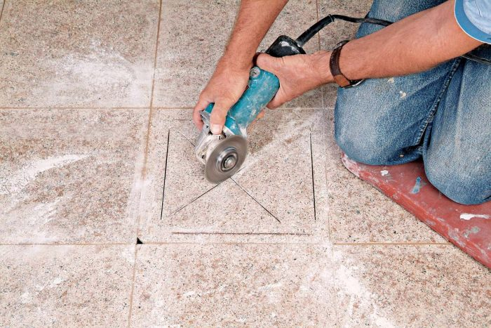 Use an angle grinder to cut an X before removing the rest of the tile.