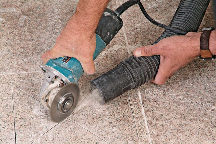 A vacuum held near the grinder will reduce the amount of airborne dust.