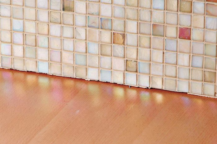 A tile splash should always be caulked at the wood and tile juncture.