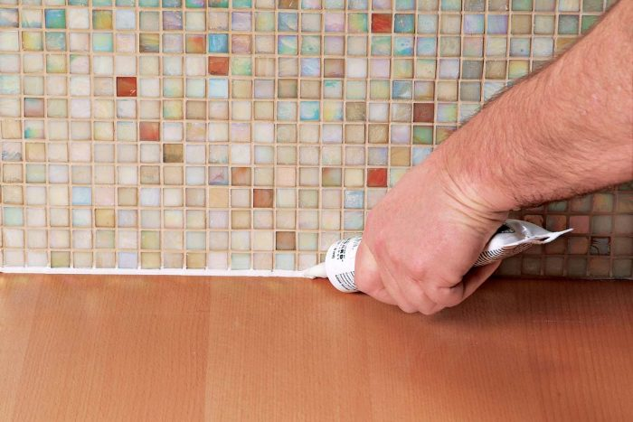 A small bead of caulk, color matched to the grout, will keep that joint flexible.