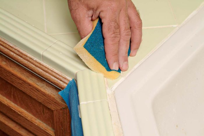 Wipe the grout with a sponge, blending the new grout with the old.