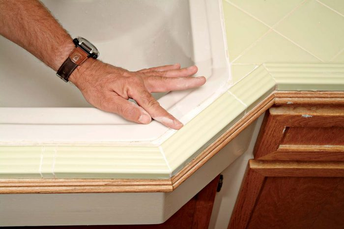 Use your finger to smooth caulk into the joint between the sink and edge tiles.