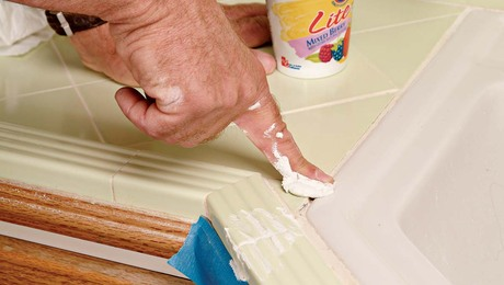 Spread the grout into the joint with a gloved or naked finger.