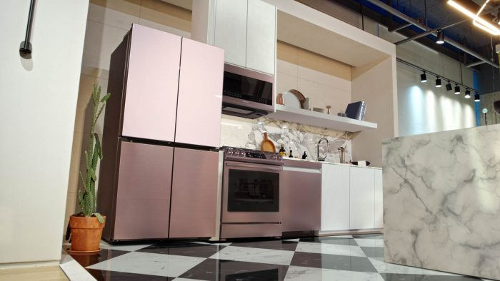 Pink refrigerator in a kitchen with a black and white checkered floor