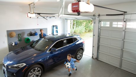 A mom and child getting our of the car in a garage