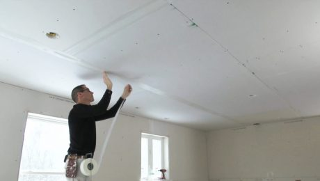 Myron taping drywall seams on the ceiling