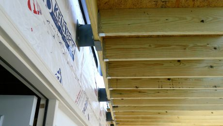 Deck ledger connecting wood beams to wall