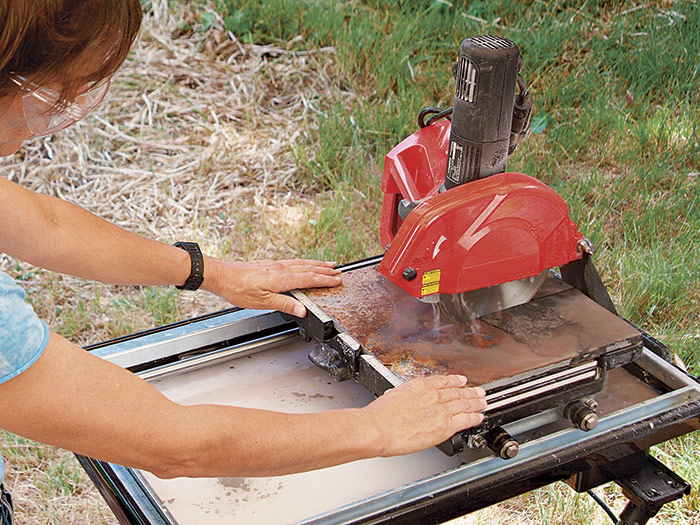 Feed the tile smoothly through the saw.