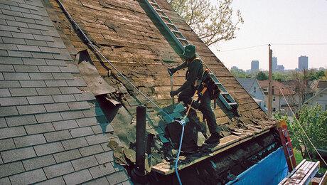 stripping old asphalt roof