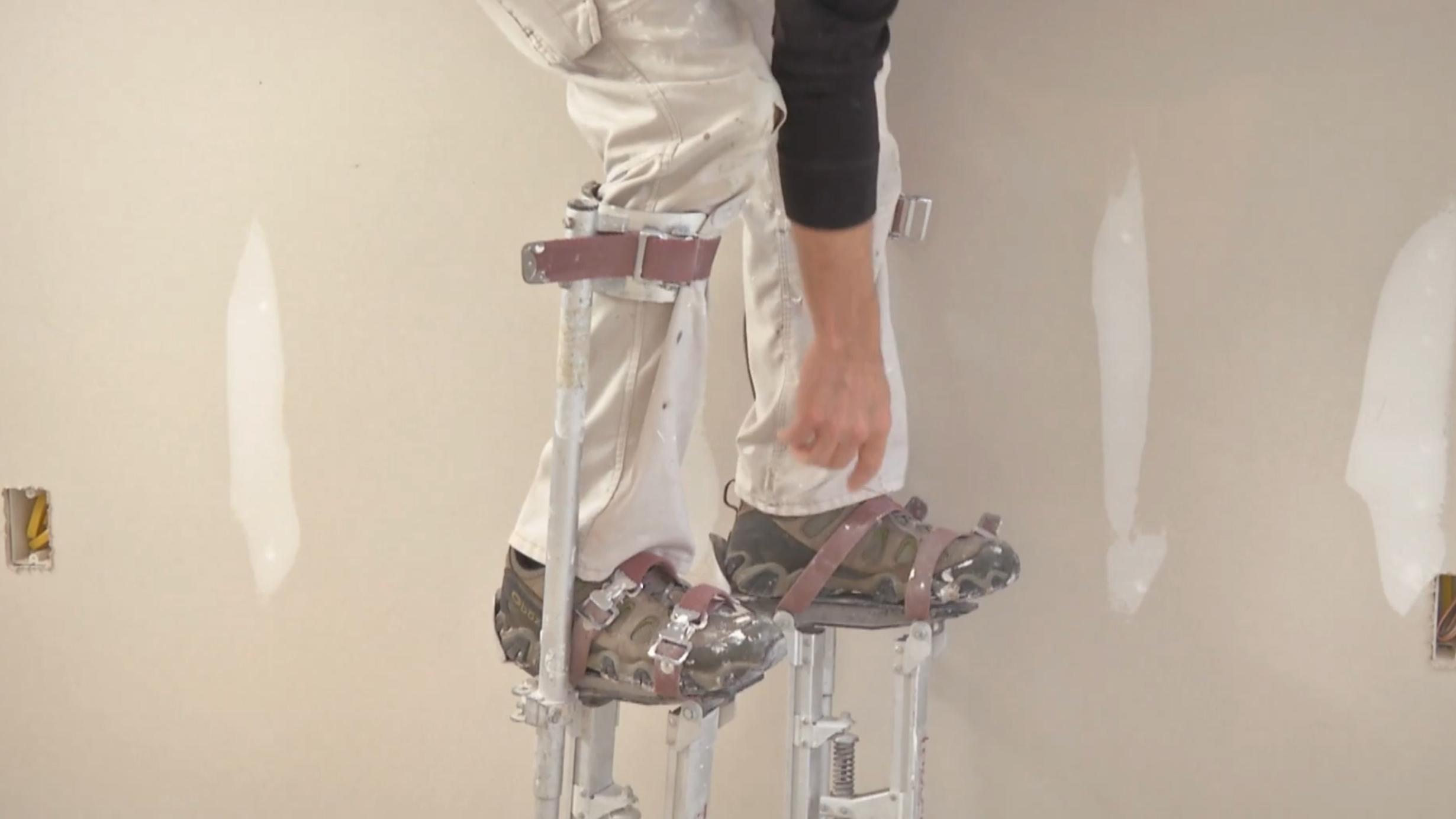 Myron climbing into a pair of metal stilts