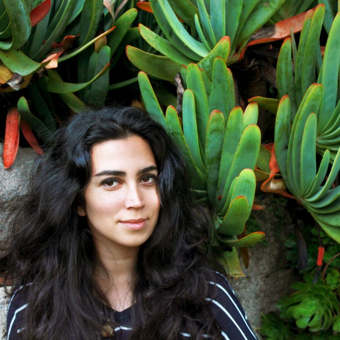 Headshot of Nahal Sohbati against a backdrop of green and red plants