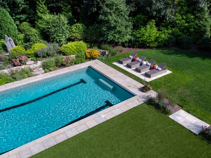 Bright blue pool surrounded by green lawn and trees