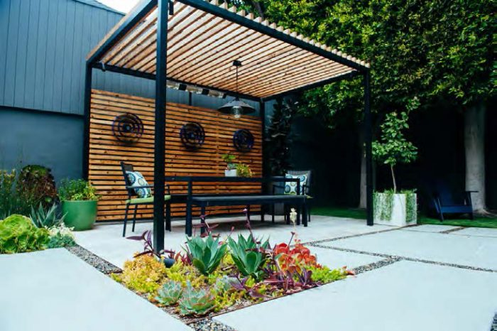 Pergola and table with large concrete pavers and plants