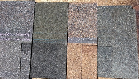 A collection of different-colored asphalt shingles lined up next to each other