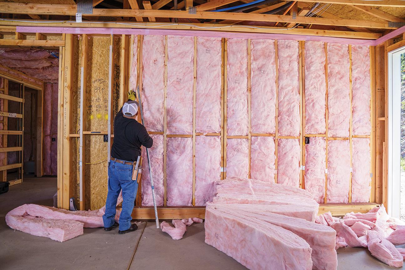 Man placing fiberglass batts between panels in a wall