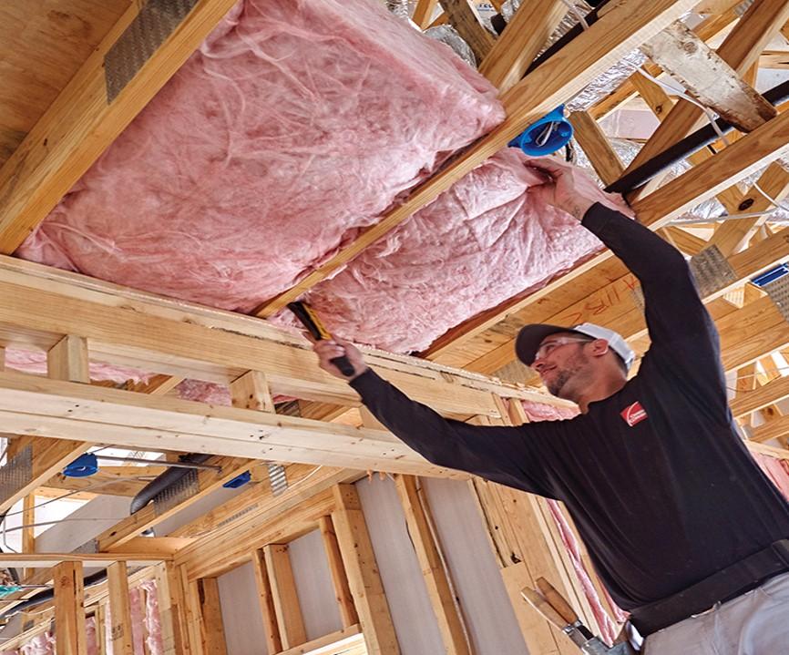 Man placing fiberglass in a ceiling