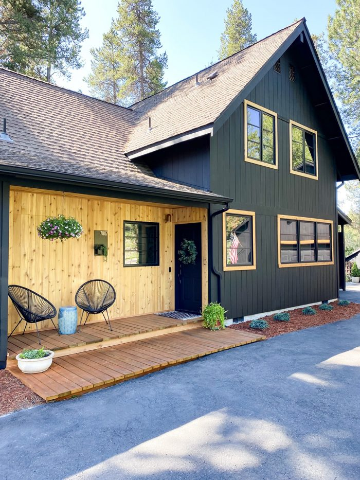 A house painted black with windows with wood trim