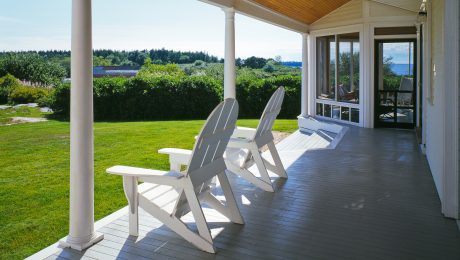 A porch with white columns overlooking a green lawn with white adirondack chairs on the floor