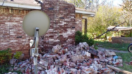 Pile of fallen bricks on the side of a house