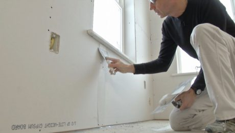 Myron smooths drywall compound on a wall with a drywall knife