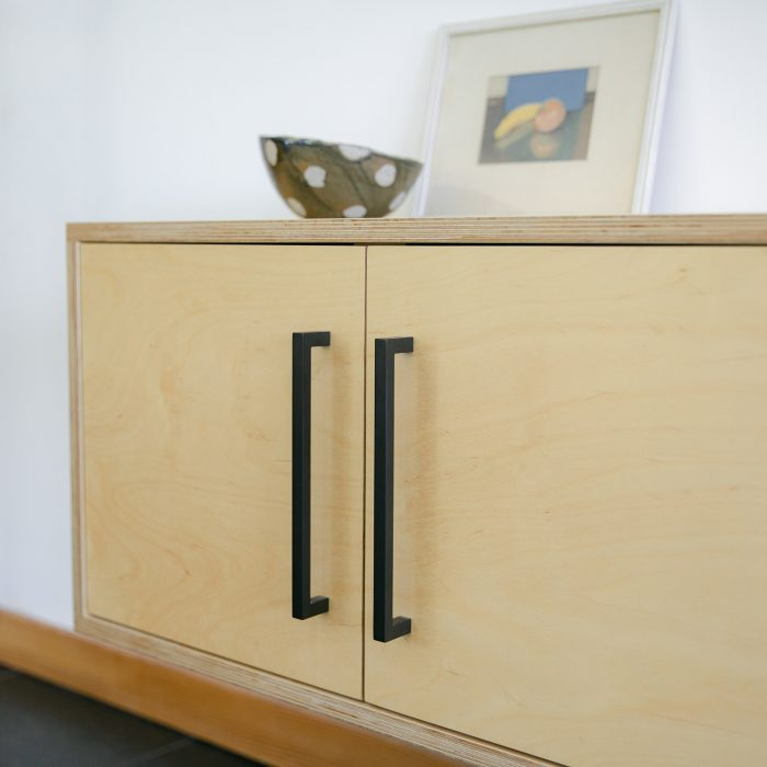 Black handles on cabinets made of light wood