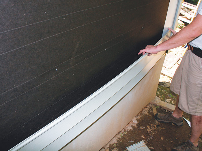 Bend vinyl siding panel to fit between J channels