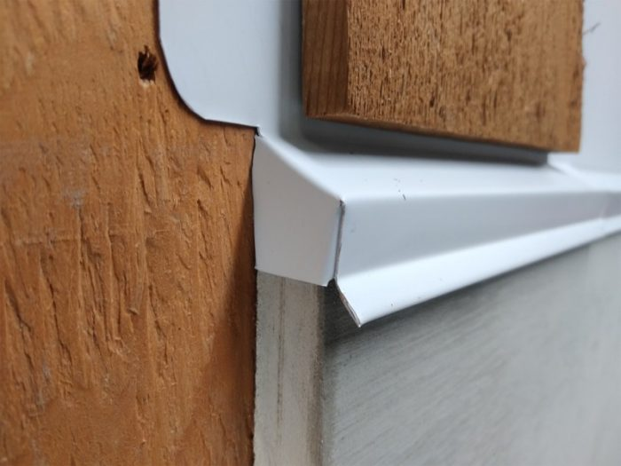 Custom aluminum drip cap with a downturned closure at the end of the trim.