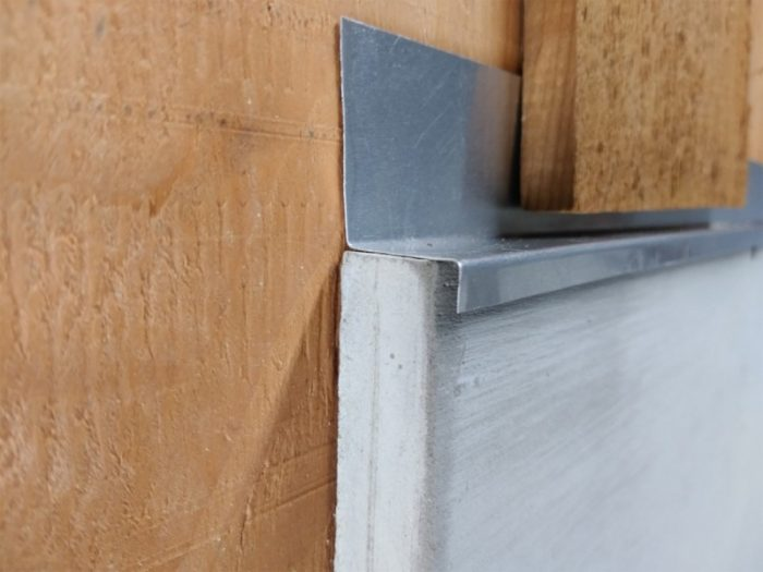Uncoated aluminum drip cap flashing over trim. It's inadequate due to short wall leg, flat cap leg and short drip leg. And the cap flashing is only half the thickness required by building code.