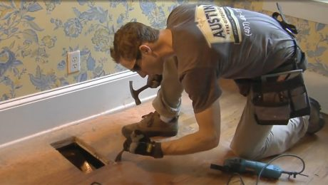 A man crouched down pulling up a floor board