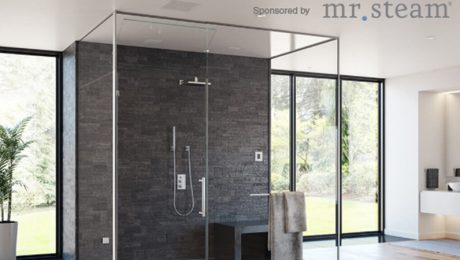 Shower with gray wall and clear glass in a room with many windows