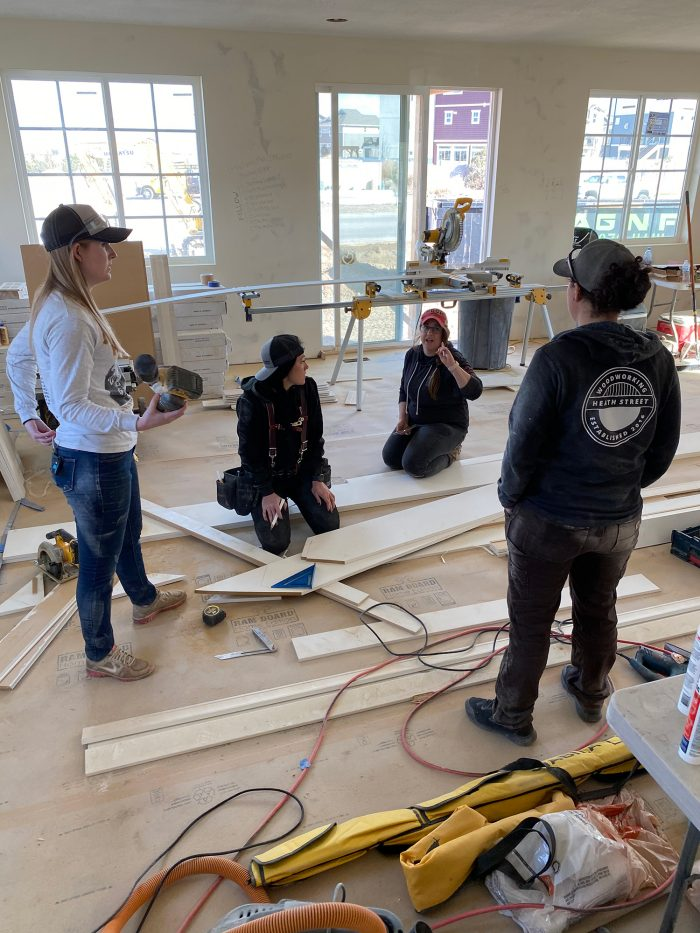A group of women in work gear collaborating around wood planks and tools