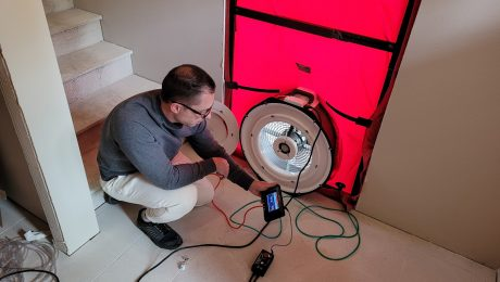 An image of Bryan crouching down by the fan of the blower door apparatus