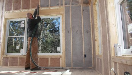 A person blowing in cellulose above a window