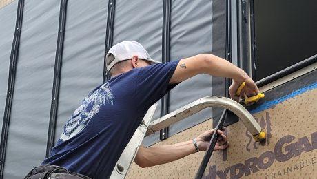 A person installing batten furring strips by a window