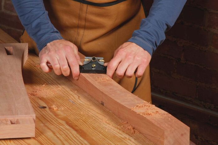 A spokeshave or card scraper works great on the curved bottom. Use a handplane on the tapers.