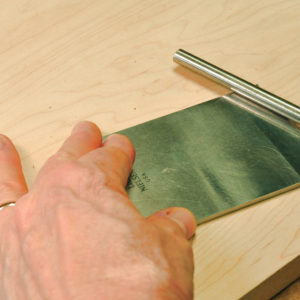 pull the blade out of the plane and slide the burnisher across the back side of the blade to mold the burr flat.