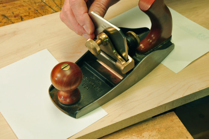 a sheet or two of printer paper under the toe of the plane, drop the blade into the holder pushing it firmly against the bench, and tighten the blade holder.
