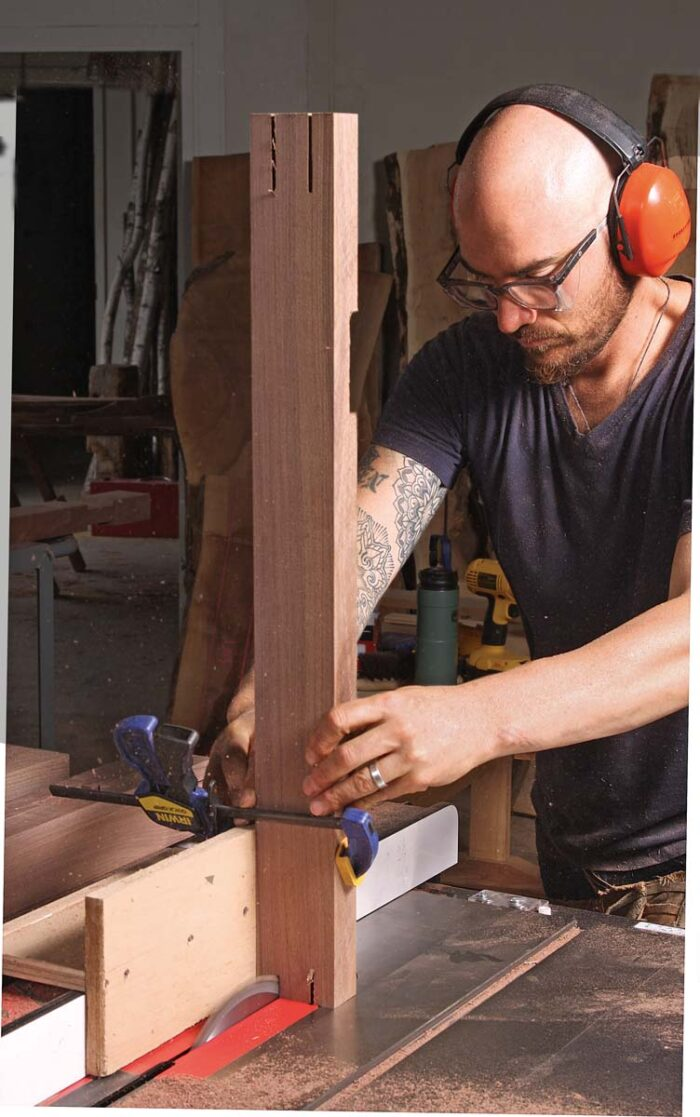 Each post gets notched on the top and bottom to complete the bridle joint on the top cross rail and foot. With the post on end in a jig on the tablesaw cut the two cheeks.