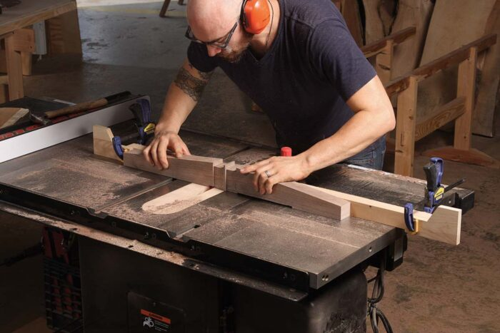 Cut the taper with a bandsaw and clean up the surfaces with a plane and sanding block. Then relieve the bottoms with a dado blade and two stops on the tablesaw.
