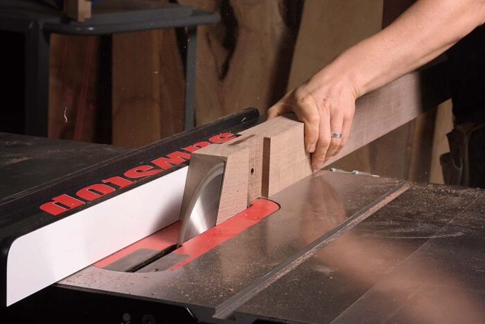 After cutting the angle on each end of the stretcher on the miter saw, use the tablesaw to trim the block beyond the half lap. With the blade fully raised, rip in and back out