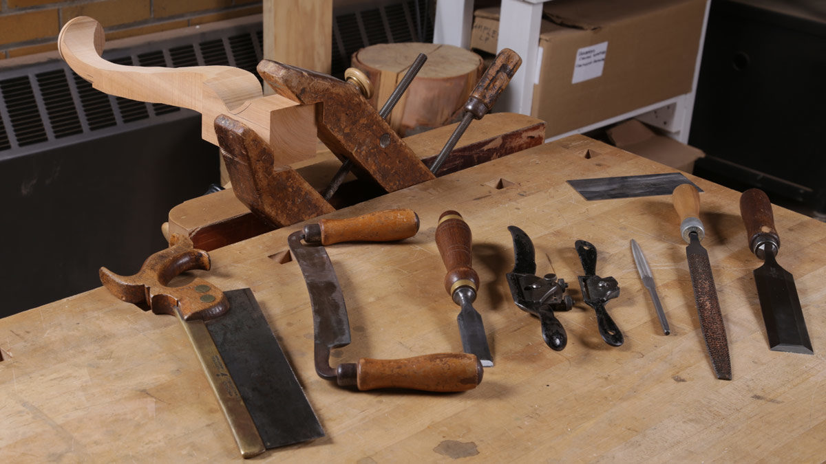 A backsaw, drawknife, a couple of chisels, spokeshaves, files, and of course, a card scraper.