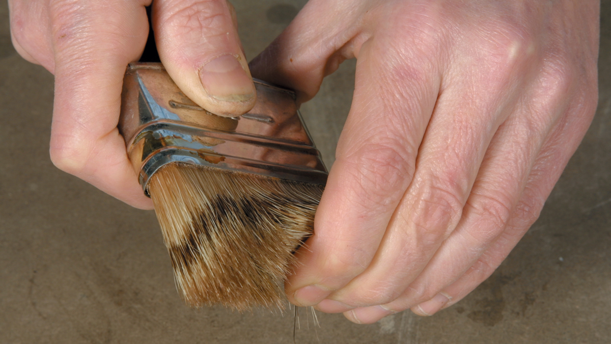 Before you use a brush, flick the bristle ends back and forth to displace dust (B).