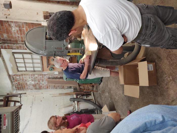 Phil Lowe at the bandsaw with people watching on
