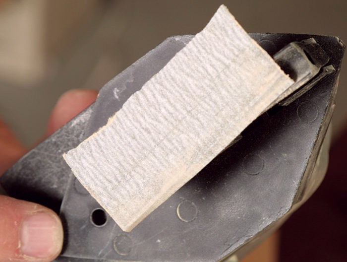 Adhesive backed sandpaper coming off the pad of a power detail sander