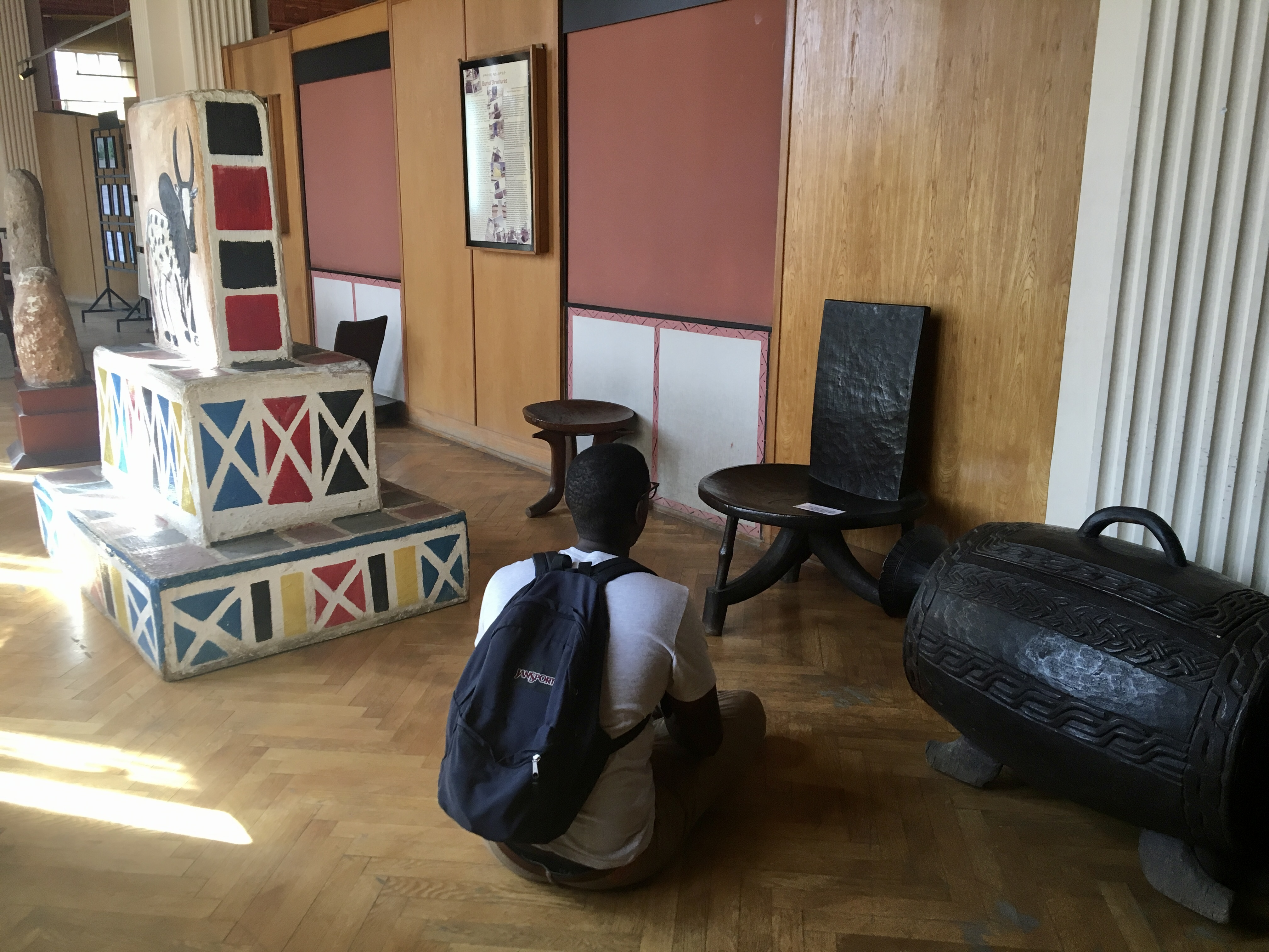 Robell sitting on the floor in a museum in Ethiopia to study a black, locally made chair. He is surrounded by sculptures.